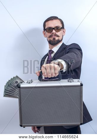 Man with eyeglasses holding a suitcase of money