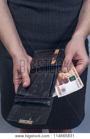 Woman in suit with leather purse full of money