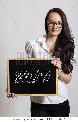24/7 - Young Businesswoman Holding Chalkboard