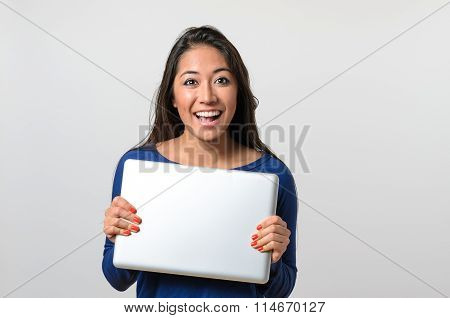 Excited Young Woman Holding A Silver Laptop
