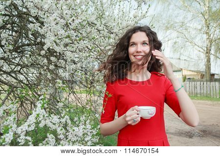 Cheerful young lady in red dress and waving hair in windy spring blooming fruit garden