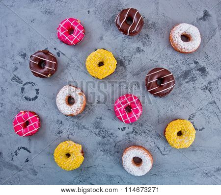 Glazed Doughnuts With Colourful Sprinkles And Icing On Dark Background