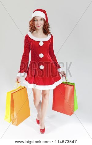 Smiling Sexy Caucasian Ginger Santa Helper Girl With Plenty Of Colorful Shopping Bags. Posing Agains