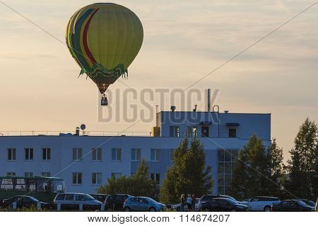 Air Balloon Levitating Over The Crowd Of People Standing Outdoors And Watching.