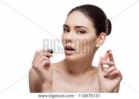 Beautiful girl applying lipgloss