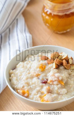 Porridge oats in bowl with dried apricots, almonds and honey. Healthy breakfast