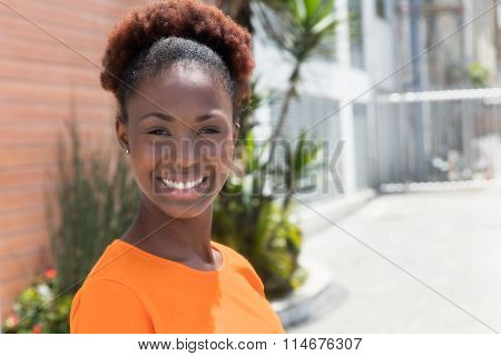Laughing African Woman In A Orange Shirt