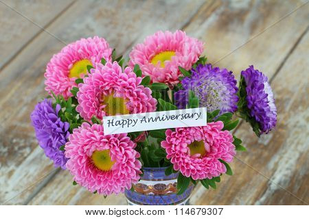 Happy Anniversary card with colorful aster flowers bouquet on rustic wooden surface