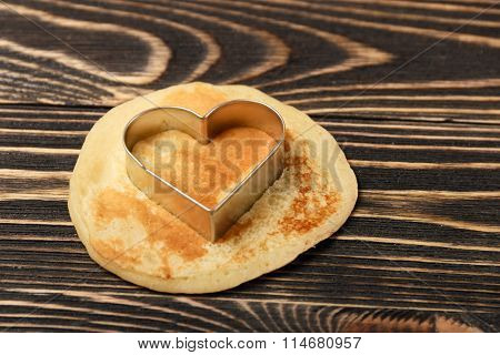 heart-shaped pancakes on wooden table