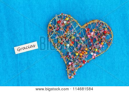 Gracias (thank you in Spanish) with heart made of colorful beads on vivid blue surface