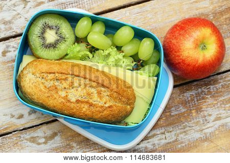 Packed lunch box containing brown cheese roll, grapes, kiwi fruit and red apple