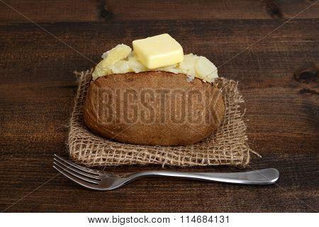 baked potato with butter and fork