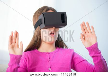 girl getting experience using VR-headset glasses of virtual reality at home