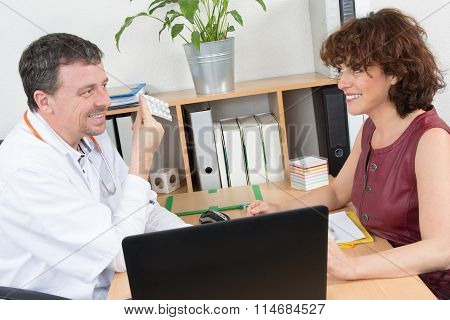 Cheerful Male Doctor Holding Pills In Front Of Female Rep