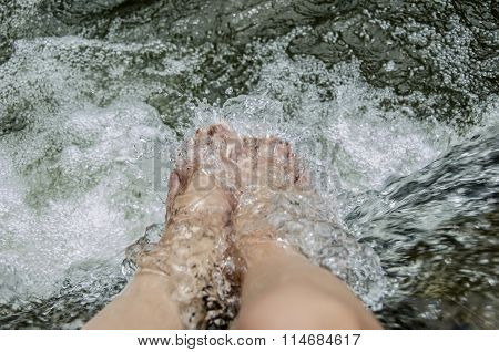 Womans feet refreshing under clear and cool water.