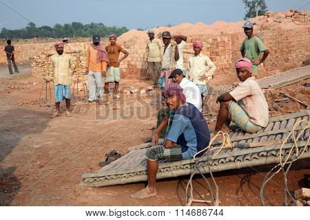 SARBERIA,INDIA, JANUARY 16: Brick field workers rest after hard work, wearing just baked brick from the kiln in truck on January 16, 2009 in Sarberia, West Bengal, India.