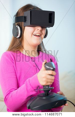 Young girl holding a gaming computer wheel getting experience using VR-headset