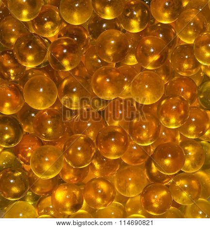 Vertical texture of the round translucent Golden yellow balls. Fish ROE, fish oil. Closeup