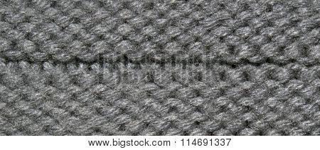 Grey texture animal fur sewn crochet with fibers and hair. Closeup