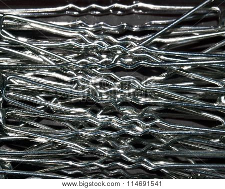 Texture of metal, silvery white wires, pins, barrettes Bobby pins. Closeup