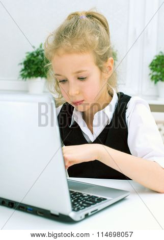 Little Girl Doing Her Homework At Home, Using Laptop.