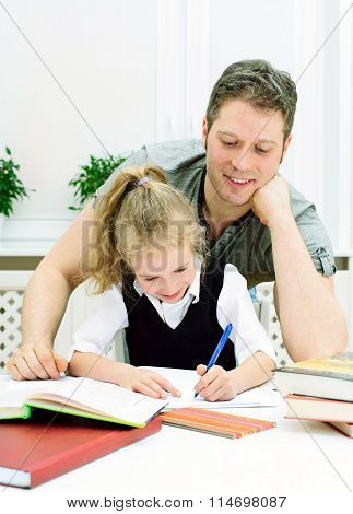 Father Helping Daughter With Homework At Home.
