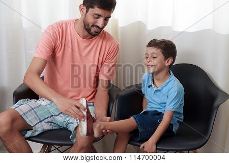 Father Putting Shoes On The Son's Foot