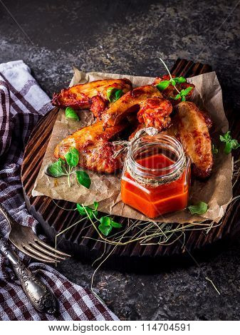 Chicken Wings With Hot Tomato Sauce On A Chopping Board