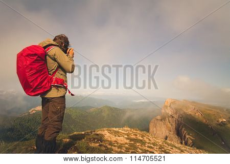 Man Traveler with photo camera and backpack