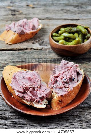 pate with dried cranberries and pickled cucumbers on a wooden background