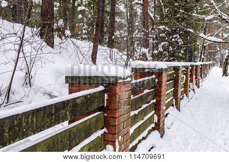 Wooden fence with stone brick columns in winter forest