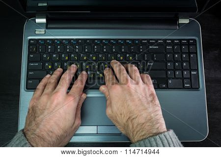 Man Typing On A Keyboard With Letters In Hebrew And English