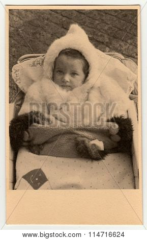 Vintage photo shows baby girl in a pram (baby carriage)