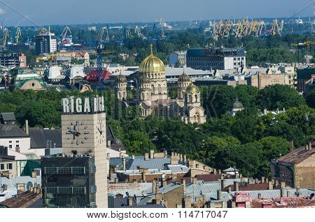 Cupolas of the Orthodox Cathedral and a clock tower with a name of the city sign on the top in Riga from above, Latvia
