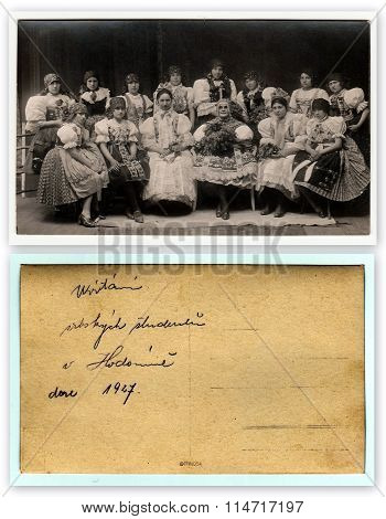 Front and back of vintage photo. Girls in folk costumes. Text in Czech - Welcome of Serbian students