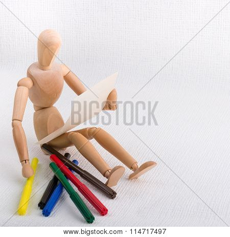 A Wooden Doll With A Piece Of Paper And Coloured Pens