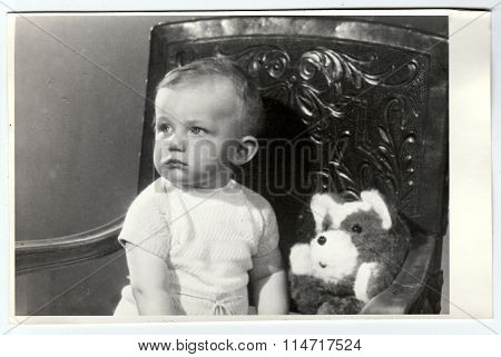 Retro photo of a small boy with teddy bear. Portrait photo was taken in photo studio
