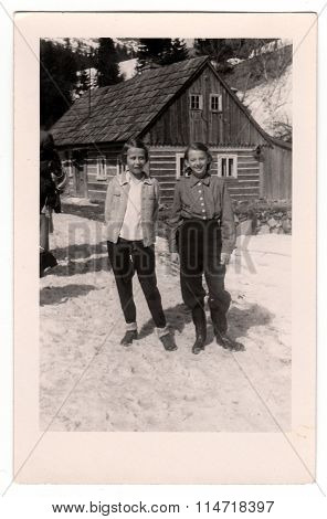 A vintage photo shows two girls in front of a log house in winter