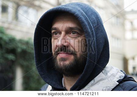 A bearded man in a hood on a city street