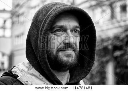 Black and white portrait of a bearded man in a hood. Street Photography