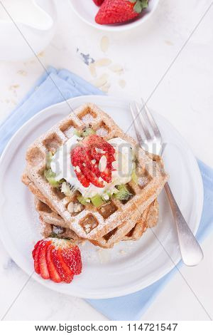 Waffles with wholewheat flour and fruits on a white plate