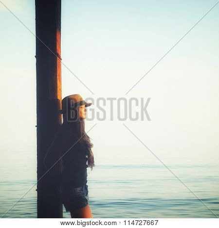 Young casual girl standing with closed eyes, relaxing under the pier in a sea water, enjoy sunset light and breathing fresh air.