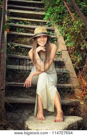 Happy smiling young woman dressed in hat and white long dress sitting barefoot on a vintage wooden stairs in park.