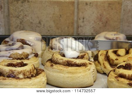Hot homemade cinnamon rolls fresh out of the oven, knife applying glaze frosting to buns