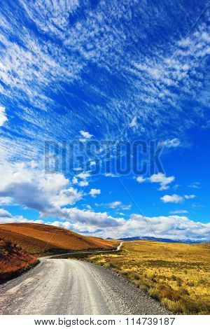 Gravel road crosses the colorful valley national park Torres del Paine in Chile. Dreamland Patagonia