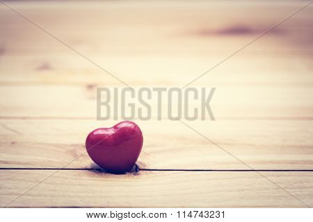 Red little heart on wood. Vintage concept of love, Valentine's Day. Copyspace for text etc.. Perfect for greeting card.