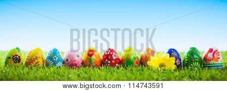 Colorful hand painted Easter eggs on grass. Banner, panoramic composition. Traditional decoration, unique handmade design.