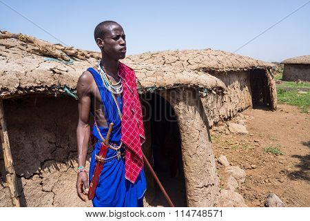 A maasai men standing in front of mud hut