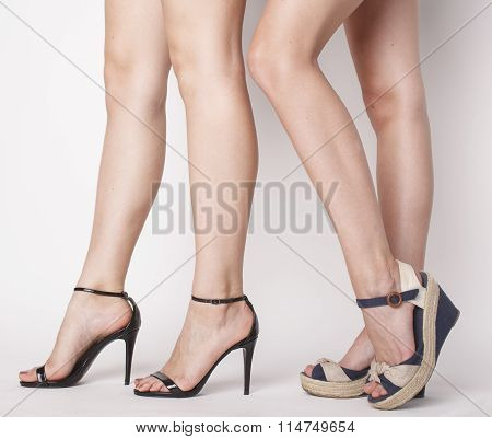 two pair of woman legs in hight heels shoes
