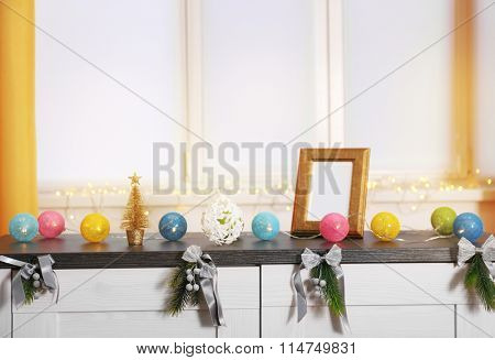 Colourful Christmas decorations on the table against window decorated with glowing lights, close up